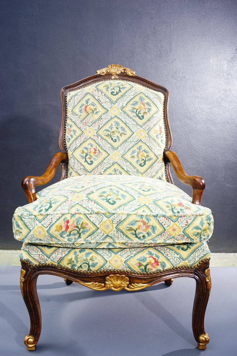 Single 18th century French carved walnut Regence armchair with gilt details. Newly upholstered in Old World Weavers material.
