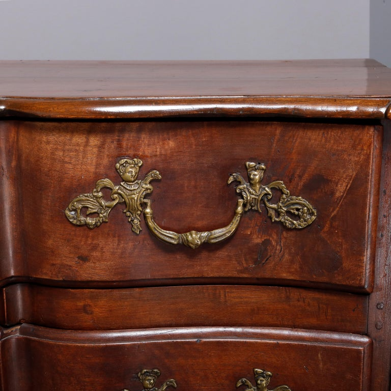 An 18th century antique French commode offers walnut pegged and paneled construction with shaped top surmounting serpentine case having three long drawers each with figural cherub cast bronze hardware, 19th century.   ***DELIVERY NOTICE – Due to