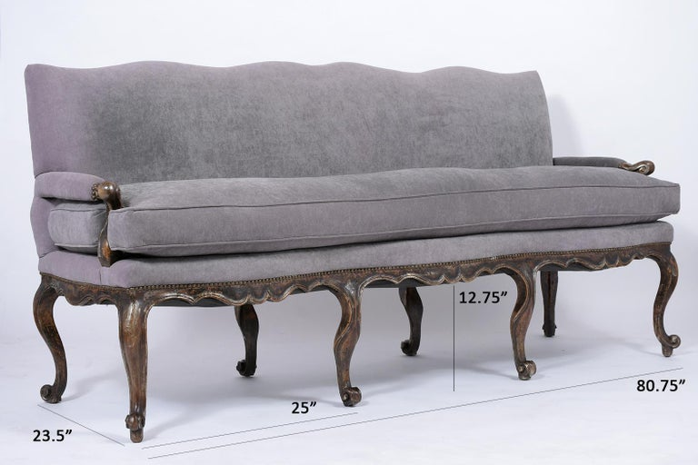 A remarkable 18th century Louis XV sofa made out of walnut wood with hand carved details throughout and features the original walnut color with silver-gilt details and beautiful patina finish. The sofa has been professionally upholstered in grey