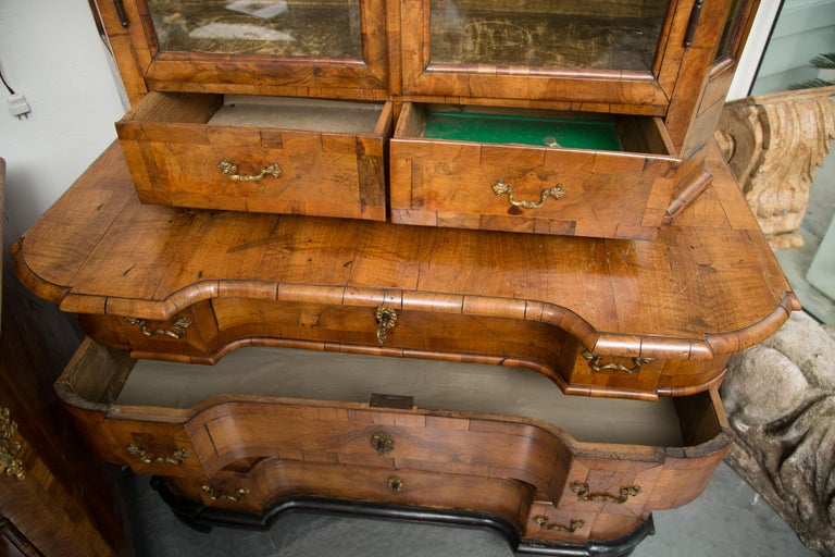 This is a very mellow George i burled walnut cabinet. There is a double domed cornice with ogee moulding over conforming top with two deep beveled glass doors and canted corners also with glass insets. The breakfront bottom has four long graduated