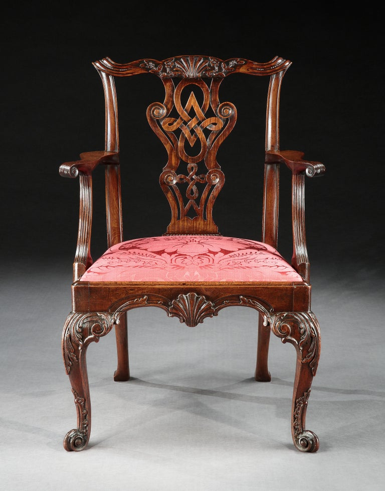 A very fine George II Irish mahogany armchair. The serpentine top rail with central scallop shell cresting above a pierced and interlaced carved back splat.