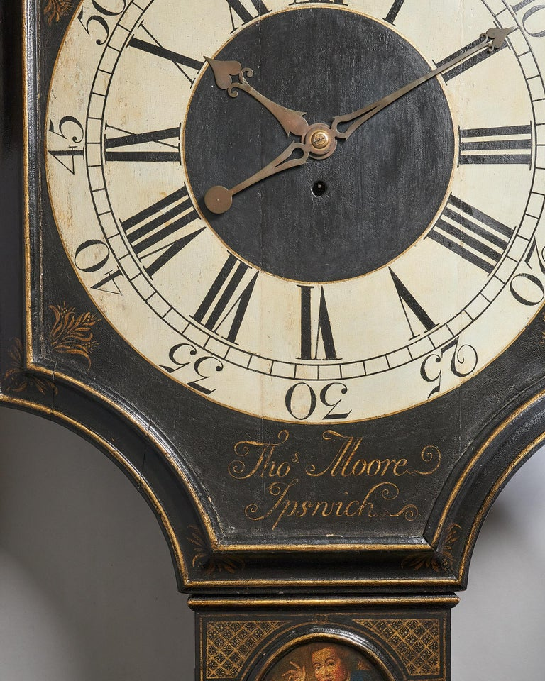 Tavern clock by Thomas Moore Ipswich  A fine eighteenth-century tavern clock with a japanned shield dial and gilt decorations, signed at the bottom of the dial in gilt letters Thos Moore Ipswich, c. 1740.   The black japanned case of traditional
