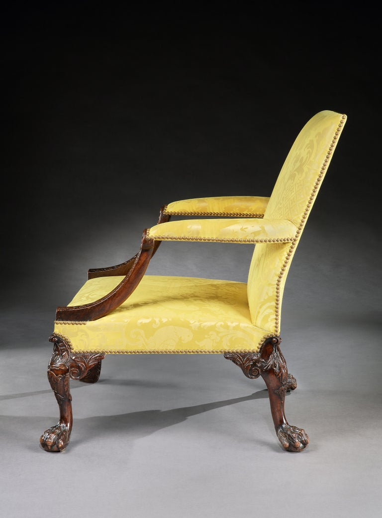 An outstanding George II walnut Gainsborough or library chair attributed to Giles Grendey. The rectangular upholstered backrest flanking a pair of upholstered outswept armrests raised on supports carved with acanthus decoration, above a square seat
