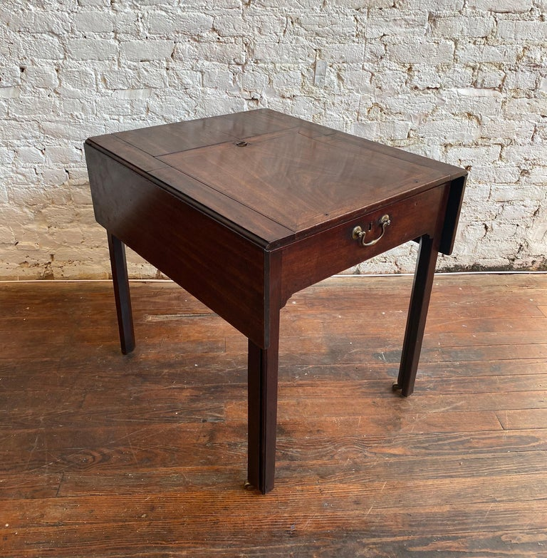 Great 18th century Georgian mahogany metamorphic architect's table. Drop-leaf form top over Marlborough legs with top lifting to 45 degrees. The front slides out on original brass castors to reveal wells and cubbies. Candle slide with carved bone