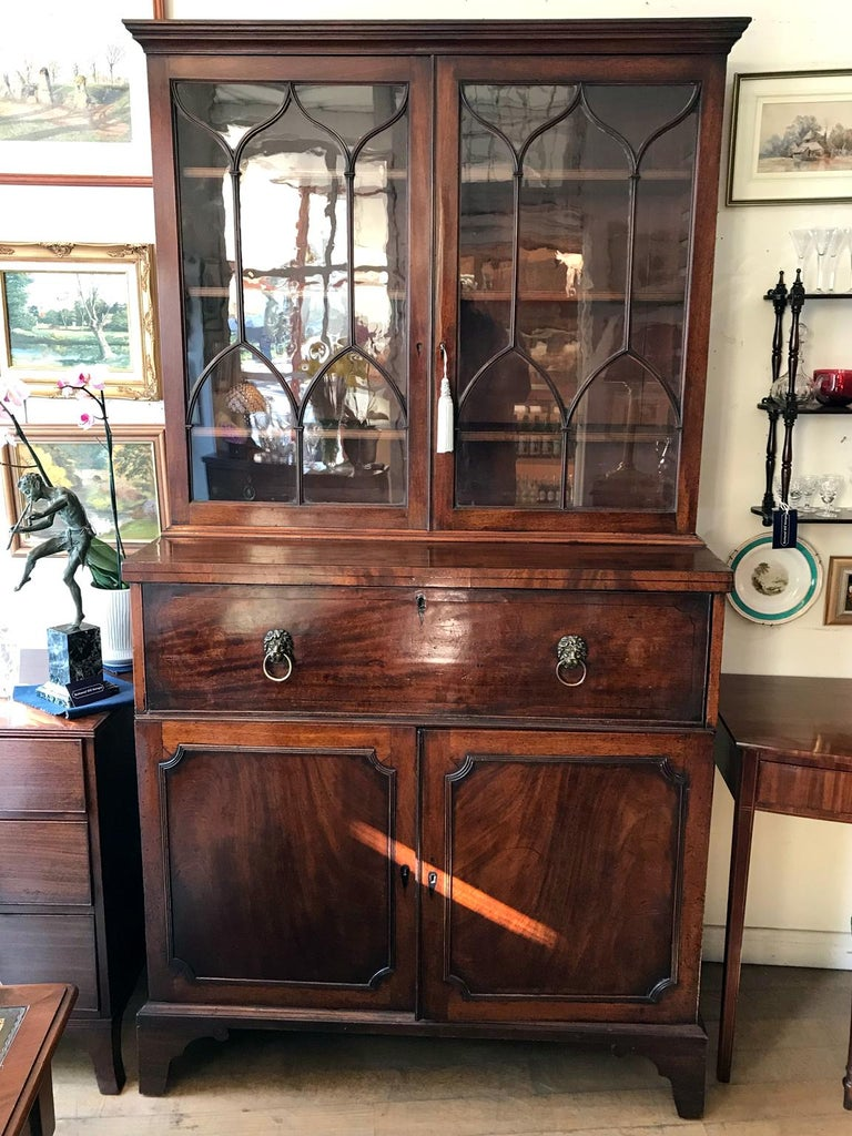 A high quality 18th century Georgian mahogany secrétaire bookcase / cupboard with two glazed doors with adjustable sliding shelves. The pullout / pull-out secretaire drawer with solid brass lion handles incloses a fitted interior with pigeon holes
