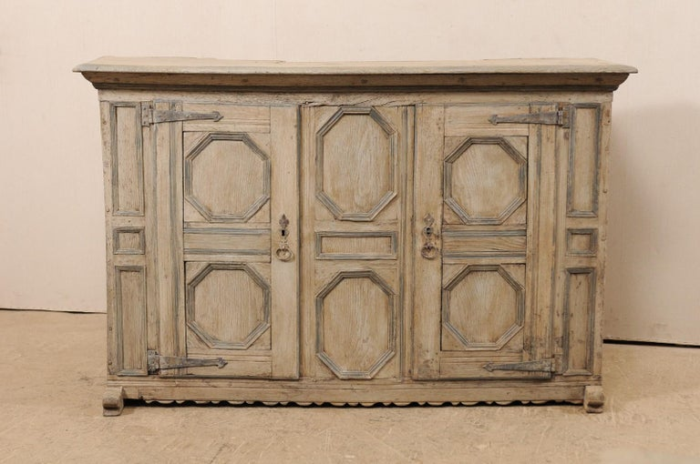 An 18th century German carved wood cabinet with geometric designs. This antique chest from Germany features a wood case with two doors heavily carved in geometric patterns, of octagonal and rectangular-shaped panels across the front side, a nicely