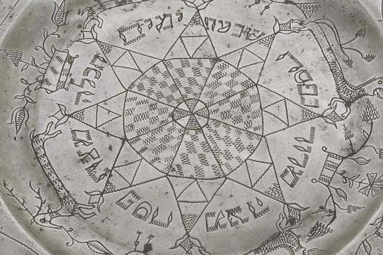Pewter passover tray, Germany, 18th century. The outer rim has wriggle- work engraving of the order of the Seder service, along with a pair of birds flanking two Hebrew letters, which are the initials of the owner of the tray. Inner rim has two