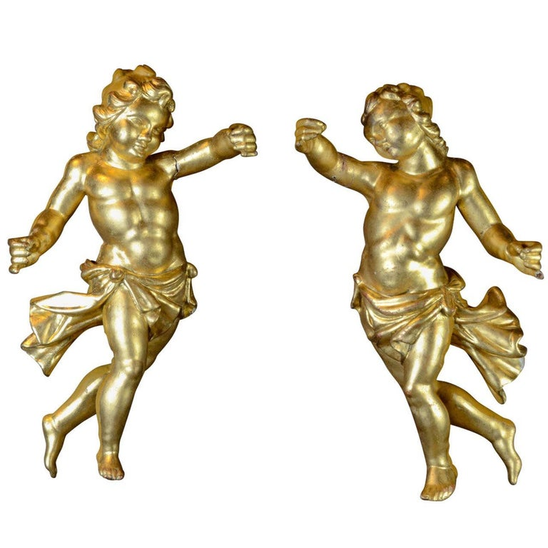 A rare and magnificent pair of ancient 18th century Italian sculptures depicting Baroque Putti.  The style, quality and workmanship of this pair of winged angels in gilded wood with gold leaf, suggest a noble production in central Italy, most