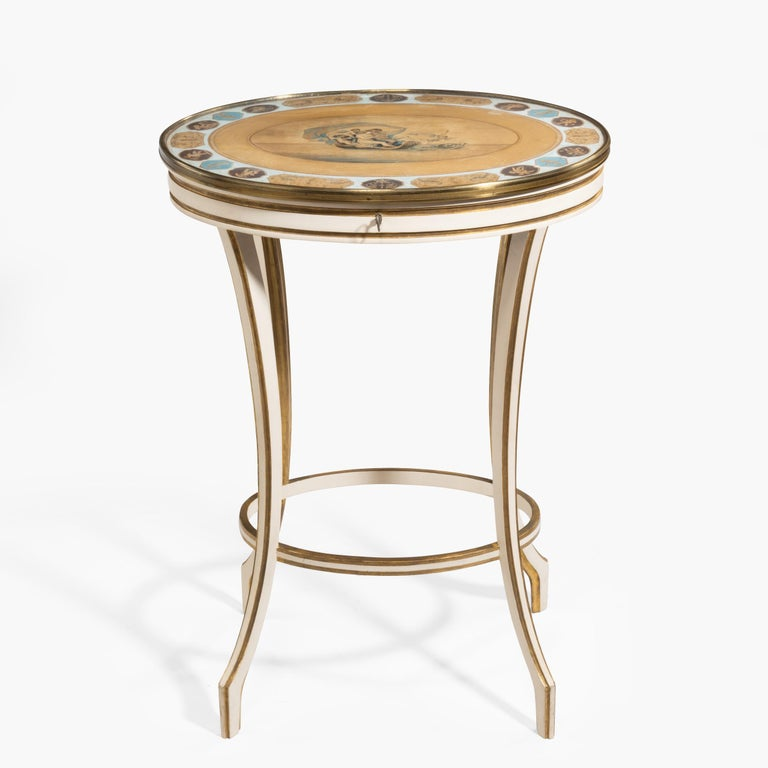 A late Adam period work table depicting Venus and Neptune  The slender gilt and white gesso decorated legs supporting a lockable oval tilt-top fitted with a mahogany-lined compartmentalised interior. The glazed top displaying a gouache of the