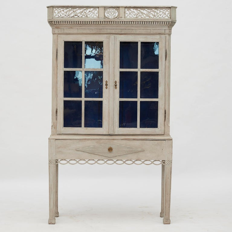 A Beautiful Danish Louis XVI (Gustavian) cabinet with paned glass doors. Light gray color with beautiful blue color inside. Original base with fake drawer front. Denmark, 1780-1790. It will serve dutifully as a display case or storage cabinet.
