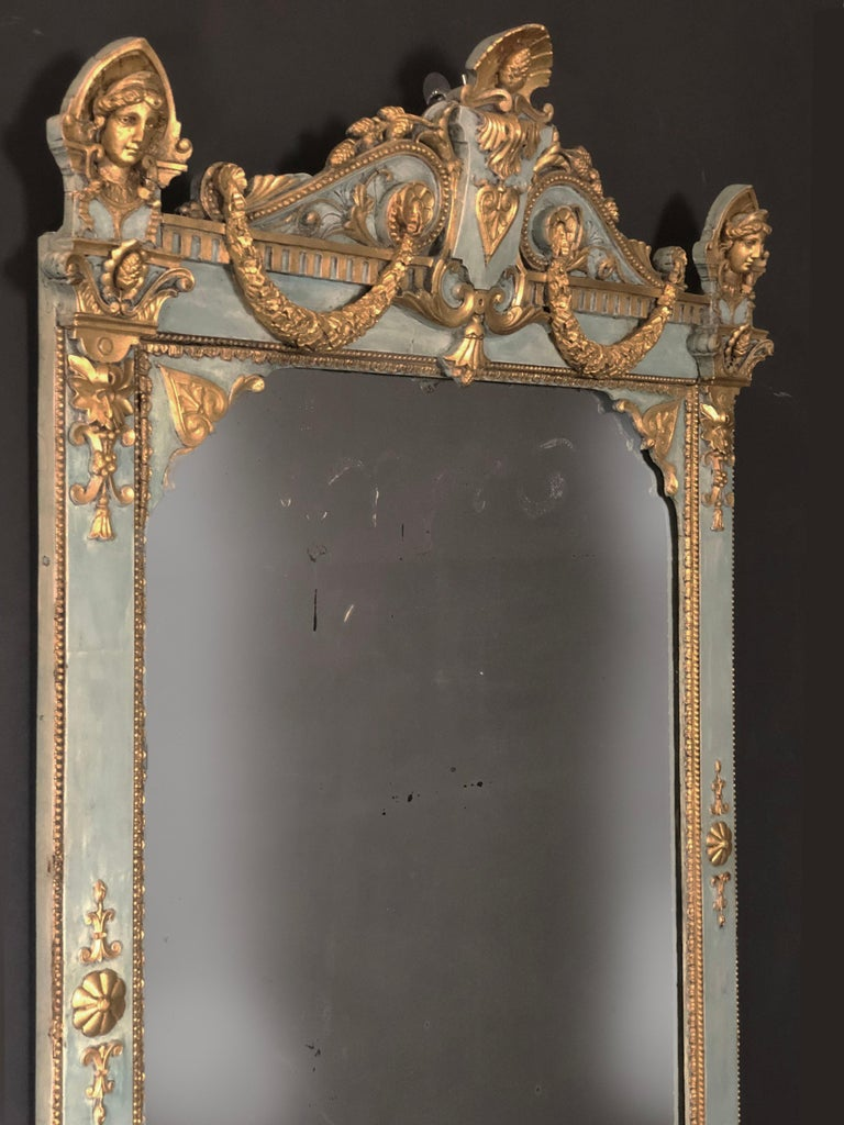 Outstanding late 18th Century Gustavian Baroque Mirror of Swedish origin, parcel gilt and painted light chalky blue with elaborate heraldic pediment featuring impressive gilded busts of caryatids and wreaths, as well as other gilt decorations