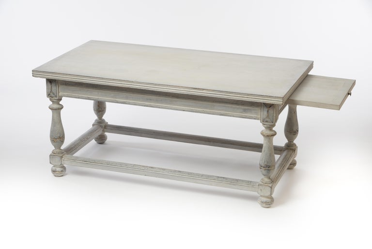 This exceptional Gustavian coffee table from the 18th century features not only interesting legs with an all-around footrest but also practical pullout extensions on each side perfect for placing an extra drink. The table is in good condition and