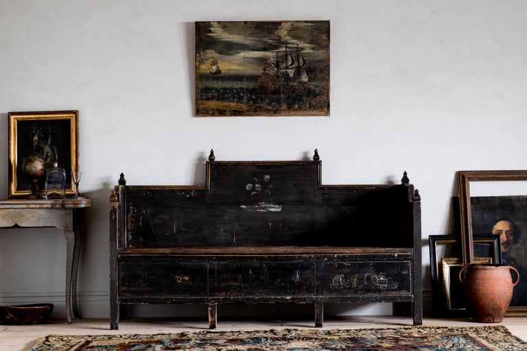 Most unusual 18th century Gustavian folk art sofa in its original black color with a good patinated surface. Wonderful naive paintings on the front and sides and the lid open for storage underneath, circa 1790 Sweden.   The condition is good with