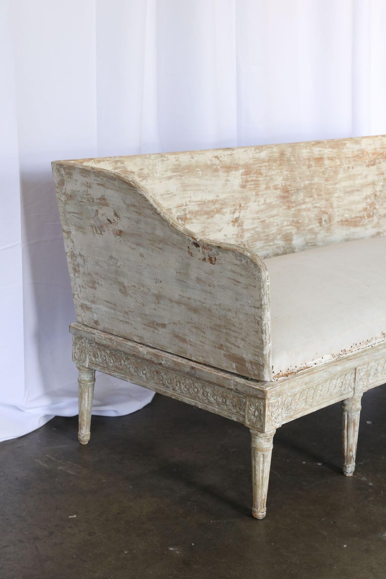 18th century Gustavian sofa with original paint dry scraped as in the European fashion. Round tapered legs and detailed carving around the sides and front of the sofa. At the top of each leg is a rectangular carved block medallion.