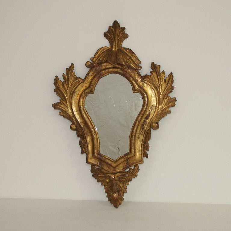 Wonderful Baroque giltwood mirror, Italy, 18th century. Weathered, small losses and old repairs.
