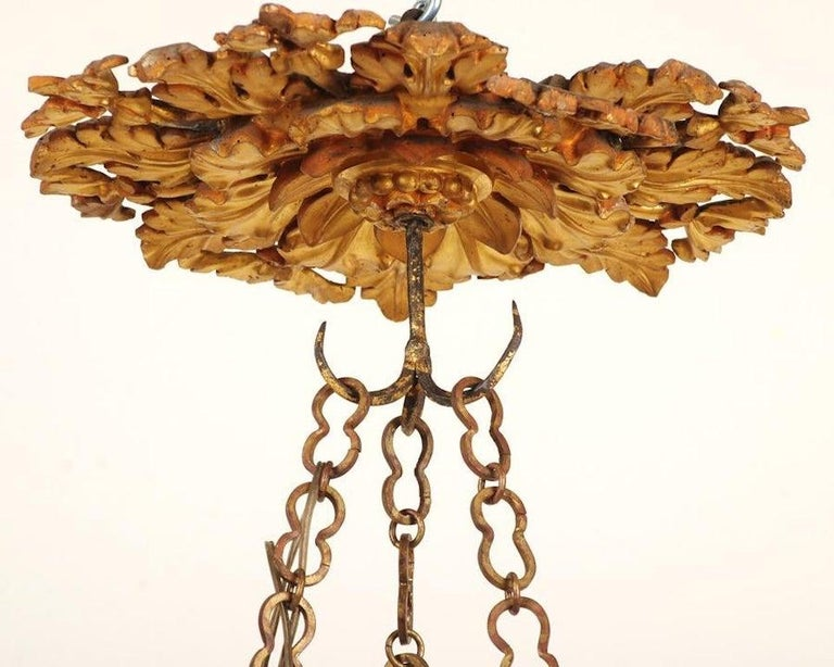 Period 18th century Italian carved and giltwood chandelier with six wrought iron arms. Intricately carved and giltwood canopy with wrought iron extension chain and carved and parcel gilt bowl.