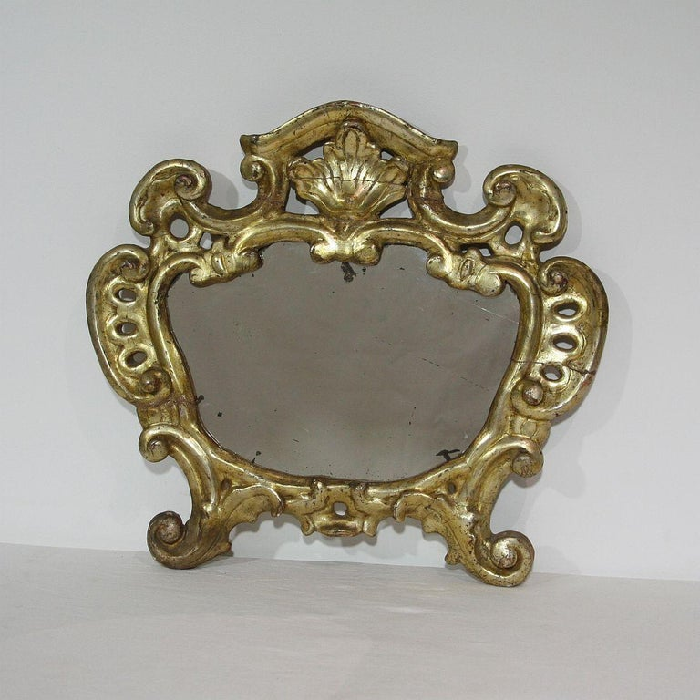 Beautiful carved giltwood baroque mirror, with original mirror glass, Italy, circa 1750. Weathered and old repairs.