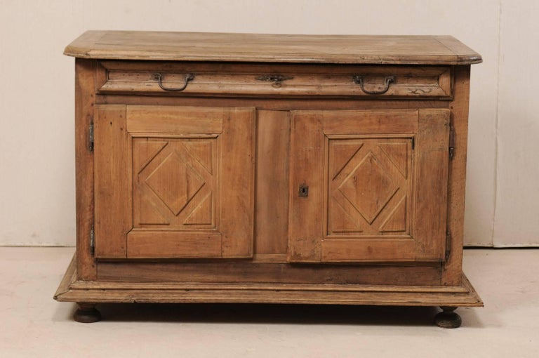An Italian 18th century two-door credenza of walnut wood. This antique cabinet from Italy features a slightly overhanging top with rounded front corners, atop a slender full length drawer and two doors below which have diamond carved recessed panel