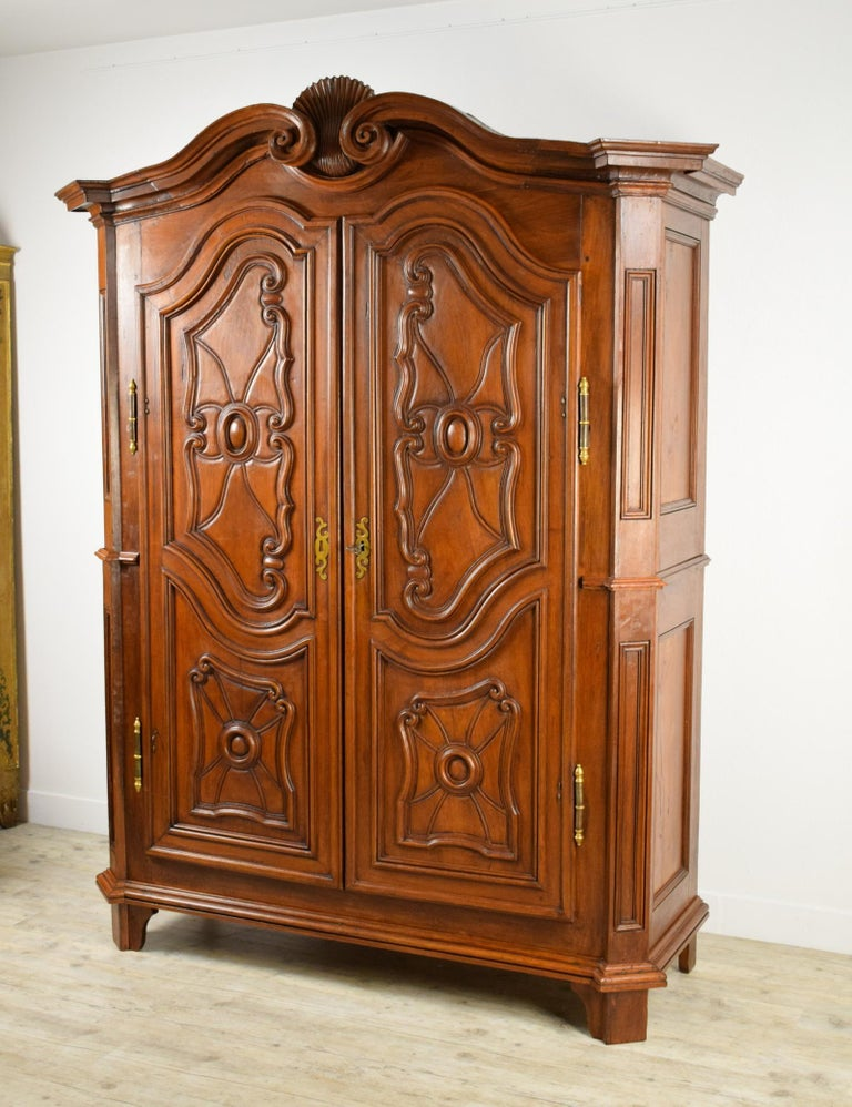 18th Century Italian Carved Walnut Wood Wardrobe   Size H 237 x W max 180; W min 168 x D 63 cm  This large and important italian piedmontese wardrobe is made of solid walnut wood. It has two moving doors, carved with a panel decoration. The