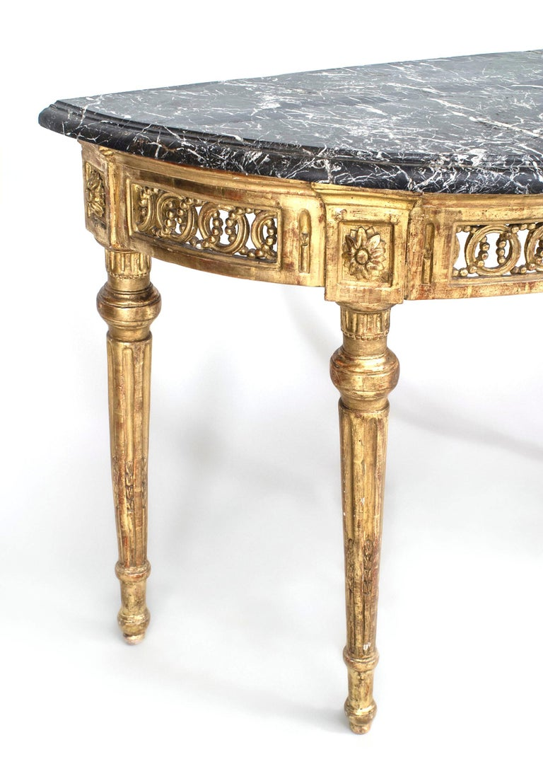 Neoclassic demilune console featuring a black marble top above an apron carved with interlocking circles, rosettes, and vertical glyphs supported by round fluted and tapered legs.