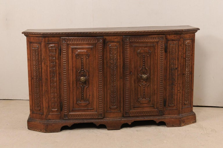 A stately Italian 18th century carved walnut sideboard. This antique buffet from Italy features rich walnut wood which has been exquisitely carved. This credenza features a slightly overhung top with egg-n-dart carvings along it's edge, the two