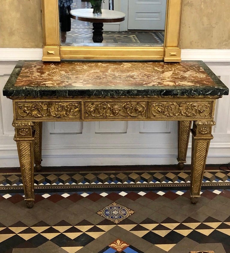 Extraordinary 18th century Italian Giltwood console table with original marble top. The Giltwood console platform has an tripartite carved frontal frieze with a central female mask flanked by scrolling leaves and bell flower swags. The consoles side