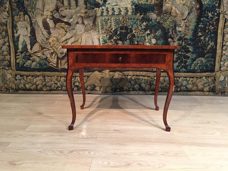 18th century, Italian Louis XV wood center desk  This elegant Louis XV desk, made in Tuscany, Italy, in the 18th century, is paved with several precious wooden essences, such as rosewood, bois de rose, walnut and, for the interiors, olive wood.