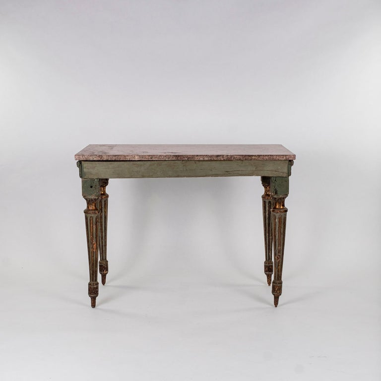 Period 18th century Italian Louis XVI console table with rouge marble top. Console is raised by fluted tapered legs and decorated with ribbons and rosettes.