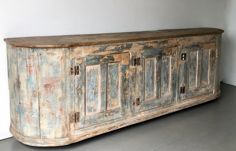 Incredible, long, very patinated with original blue color Italian, 18th century Sideboard with three paneled large doors under natural rounded shape blank top. (Photographed with moving dollies underneath) More than ever, we selected the best, the