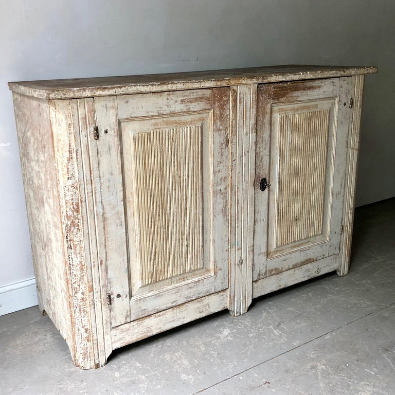A very large, richly carved Gustavian period sideboard has reeded panelled doors and reeded corner posts in wonderful worn pale bluish/grey patina. This antique sideboard offers plenty of practical storage, Stockholm, Sweden, circa 1790-1800.