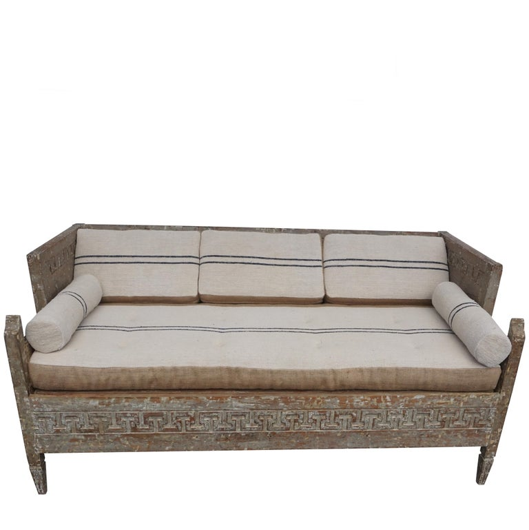 An antique Lit Du Jour, Swedish Gustavian day bed made of hand carved pinewood and fabric. This charming wood sofa was scraped to its original finish. Hand carved Greek key ornaments with an expandable storage space below sitting area, in good