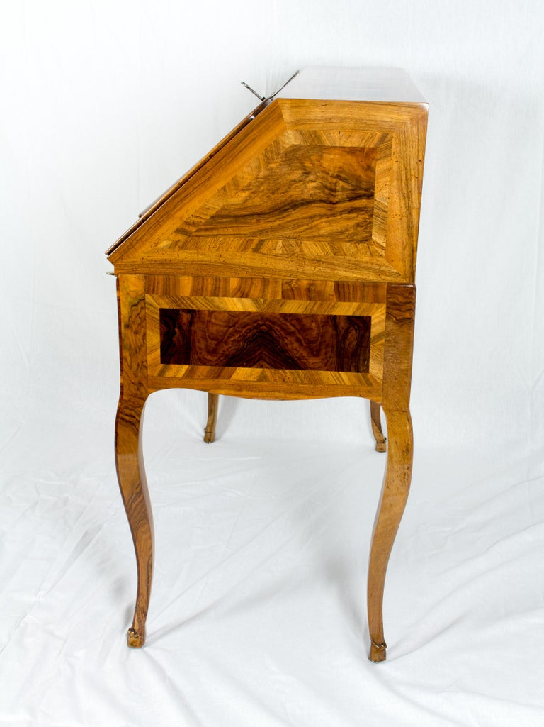 The desk is from the time around 1730 and covered with a beautiful marquetry of different walnut / walnut root wood on a pine body. All three locks are original from that time as well as the fittings.  The Secretaire is in very good restored