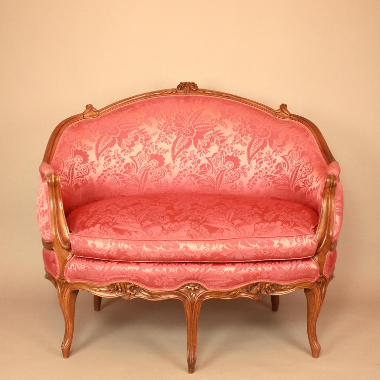 An 18th century Louis XV carved walnut settee 'canapé en corbeille' attributed to Pierre Nogaret (1718 - August 23, 1771). The padded back with a cresting centred by a flower carved spray, above padded armrest and a loose cushion seat, covered in a