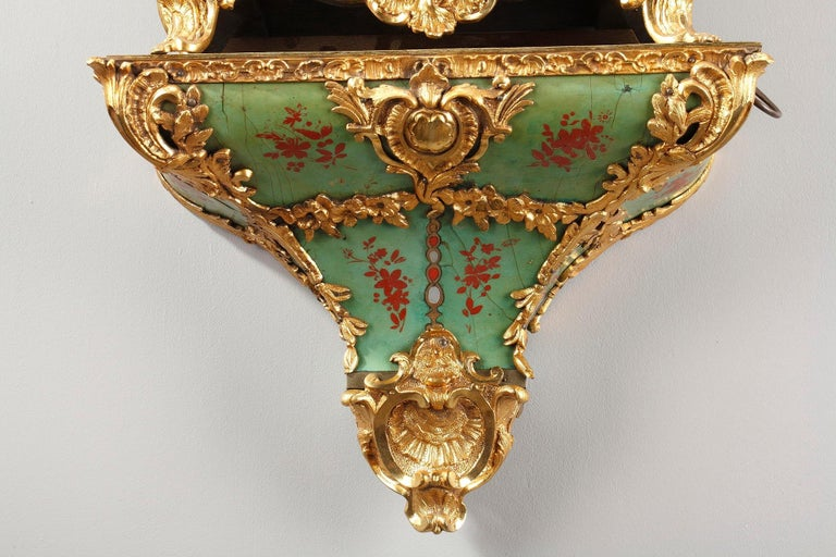 Louis XV cartel clock and wall console crafted of green horn and gilt bronze Rocaille decoration composed of foliated scrolls, flowers and vase. The horn is embellished with red bunches of flowers. The clock rests on four small arched feet decorated