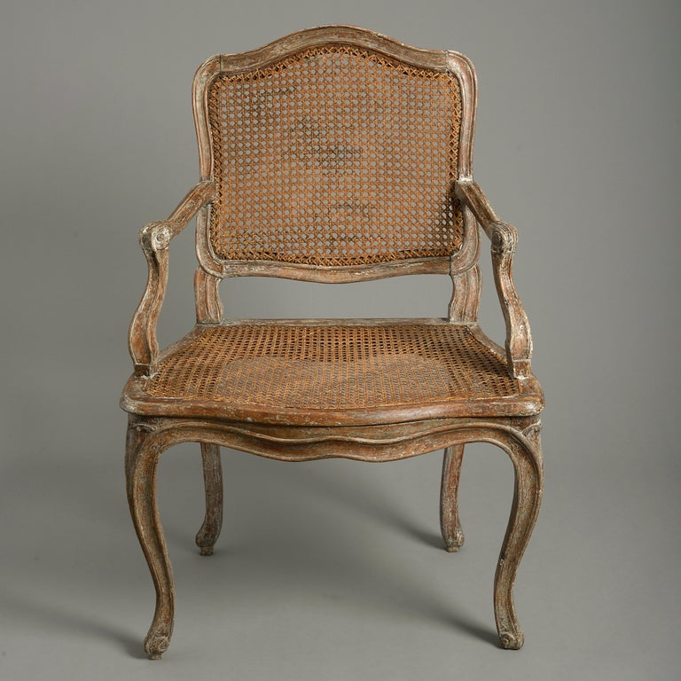 A mid-18th century Louis XV Period painted fauteuil or open armchair, the cartouche back and seat with caning, having scrolling arms and raised upon cabriole legs.