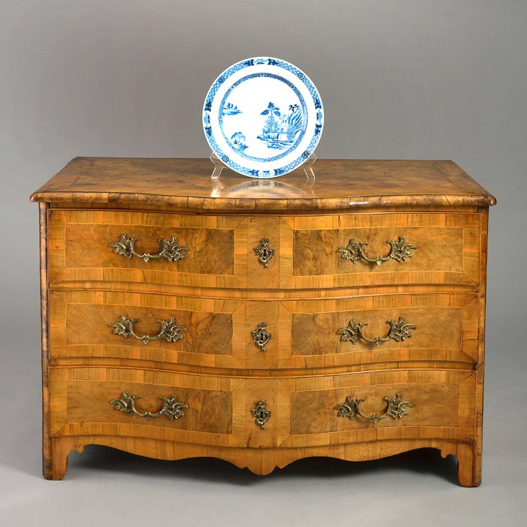 An 18th century Louis XV period commode of serpentine form, the overhanging parquetry top with crossbanding above three long paneled drawers with brass Rococo handles and lock escutcheons and terminating in a shaped apron raised upon bracket feet.
