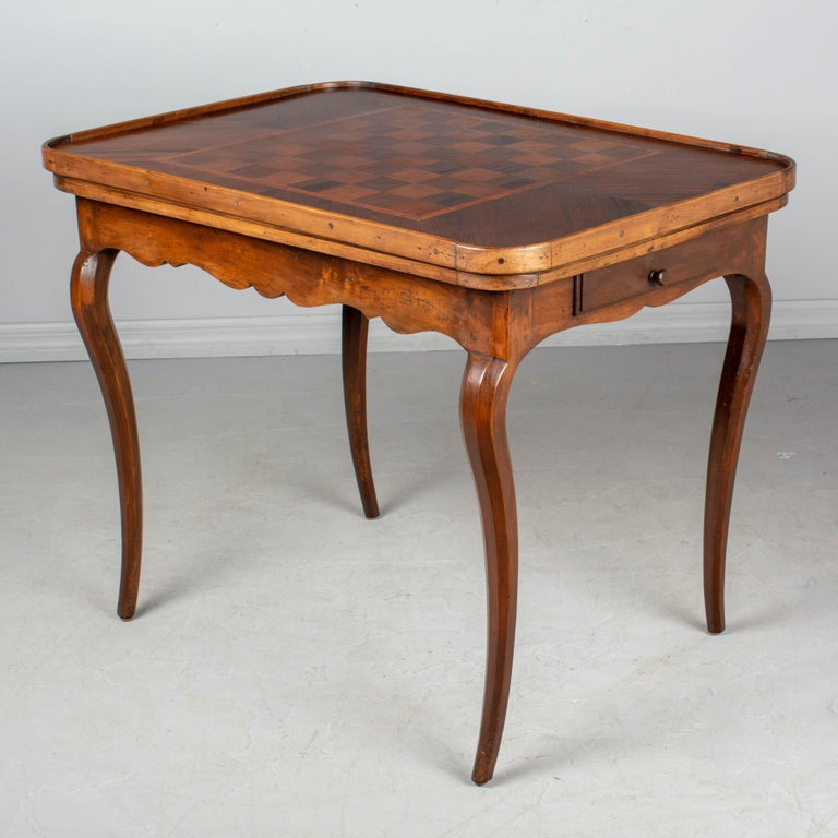 An 18th century French Louis XV style game table made of solid walnut with scalloped apron and curved legs. Removable rounded corner top with checkerboard marquetry game board on one side and a leather surface on the other. When the top is removed a