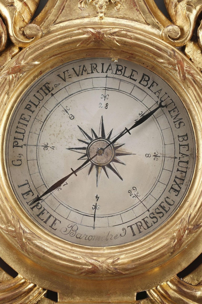 Late 18th century Louis XVI barometer and thermometer. The giltwood case is ornamented with flowery basket and foliage. The dial marked with ink on paper, allows reading of current barometric pressure. It is flanked by cornucopias and draperies. The