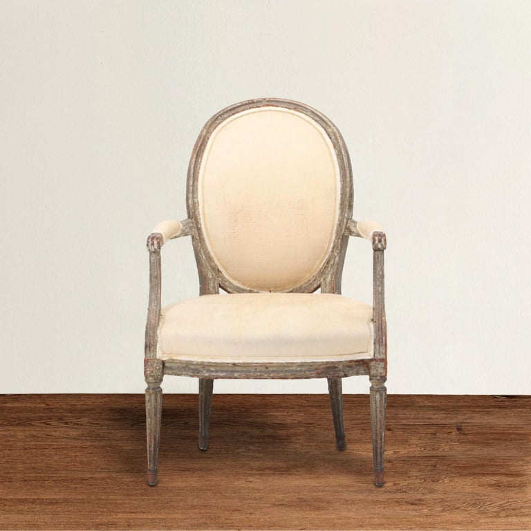 A wonderful 18th century French Louis XVI period fauteuil armchair with a large oval back, a generous wide seat, and tapered fluted legs. Chair retains traces of its original gray paint. Upholstered in a neutral canvas with tape trim, but with