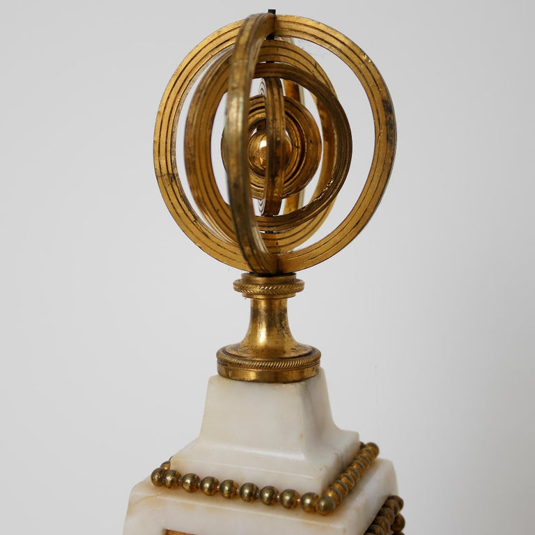 Signed: Joseph Gay Horloger du Roy A Turin  The movement is contained in a white marble obelisk which is surmounted by an armillary sphere finial. The front with a panel chased with nymphs supporting a globe with Cupid standing on top; below are