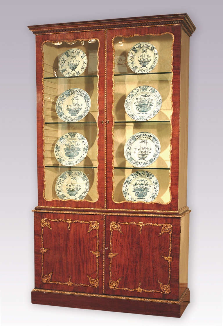 An attractive mid-18th century figured mahogany display bookcase with gilt gesso mouldings throughout having dentil moulded cornice above shaped glazed doors and paneled cupboard doors below, enclosing drawers with original swan-neck handles. The