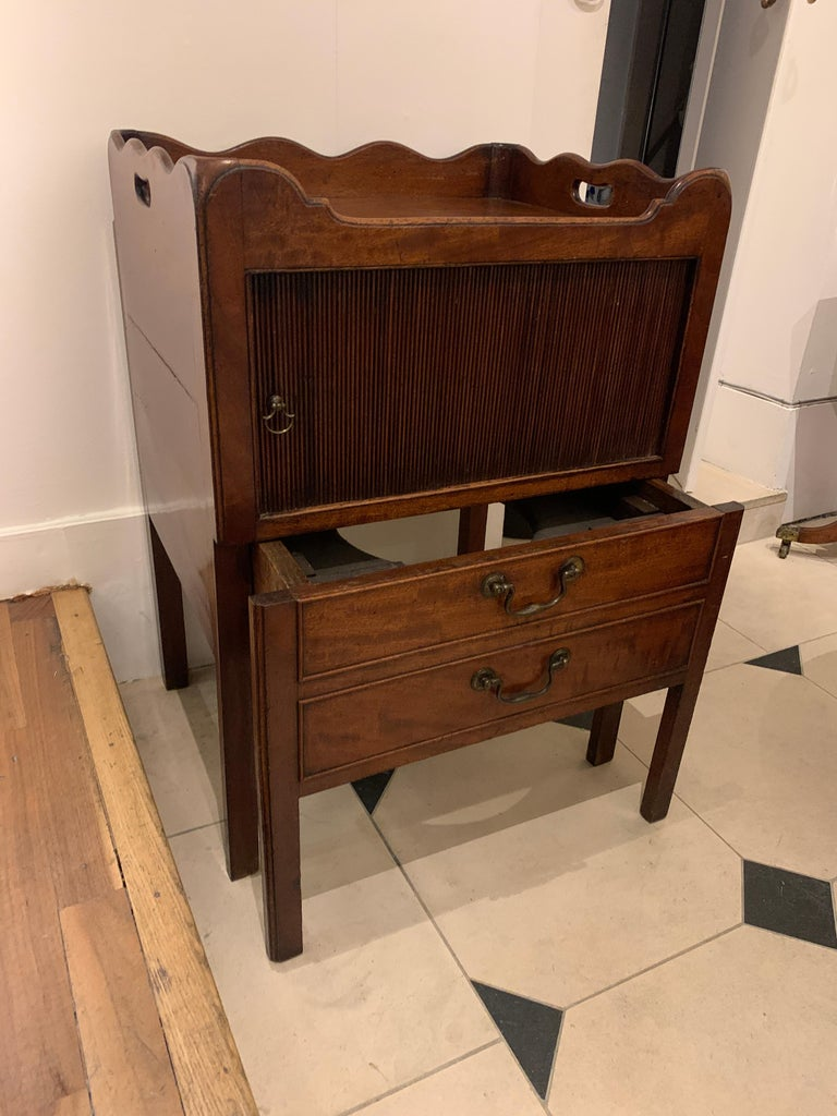 A mahogany bedside cabinet/commode with a tray top and sliding tambour door, above two drawers with brass handles,  circa 1780  Measures: Height 79cm Width 55.5 cm Depth 45.5 cm.