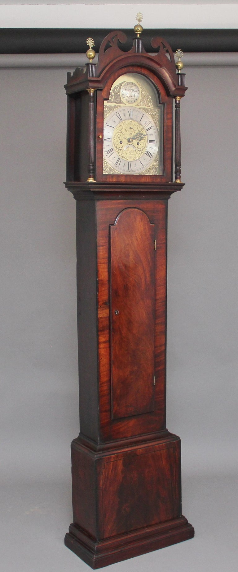 18th century mahogany long case clock by Thomas Elliott of London, it has an arch dial with a brass face and silvered chapter ring, the hood has turned and fluted columns either side of the door with brass capitals, the hood also has a lovely shaped