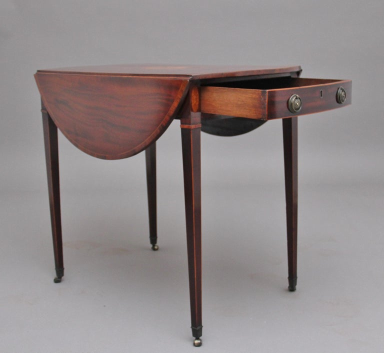 18th century inlaid mahogany Pembroke table, the crossbanded oval top decorated with shell inlay pattern at the centre, having an oak lined frieze drawer with original brass ring handles and a faux drawer the other end, supported on square tapering