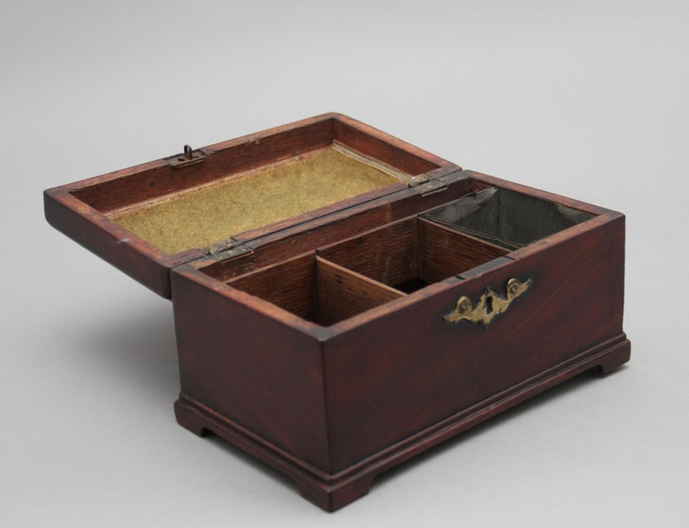 18th century mahogany tea caddy in the Chippendale style, having the original brass swan neck handle and escutcheon, the hinged top opens to reveal three divisions, with one division having the original tin canister for the tea, standing on small