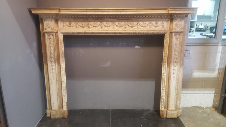 A very fine late 18th century neoclassical pine mantel in excellent condition and exquisitely well carved featuring corner blocks carved with rosettes above tapering pilasters carved with pendant bell drops, and running frieze ribbon tied swags