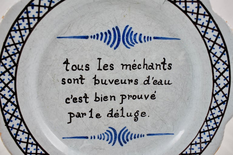 """A French Revolution tin-glazed earthenware dish, made in Nevers, circa 1790.  A hand painted motto reads in French, """"tous les méchants sont buveurs d'eau – cést bien prouvé par le déluge""""  Roughly translating to """"All of the wicked are drinkers"""