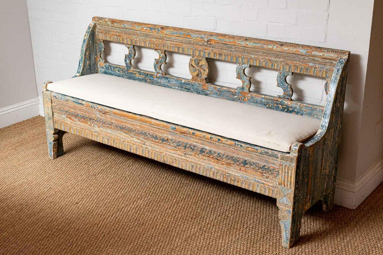Late 18th century, highly decorative, solid Norwegian bench retaining most of its original paint in different shades of blue. The bench is hand carved to the front with decorative scroll detail at the back. It has a simply covered upholstered drop