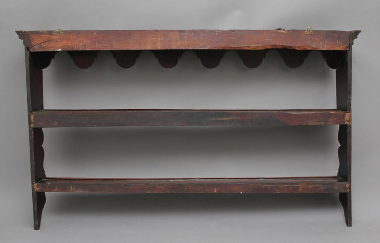 18th century oak hanging plate rack with two shelves and a shaped top and sides, circa 1780.
