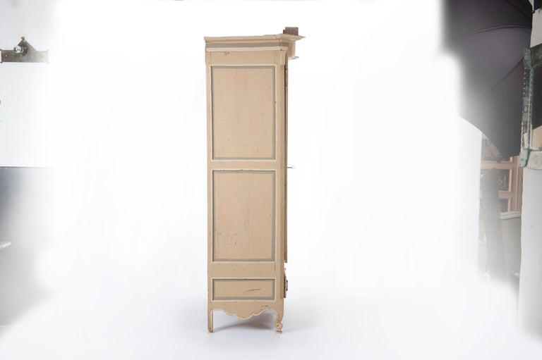 French 18th century Rococo painted wood cabinet from Provence with one curved and molded door, one chest, curving feet and cornice.  Painted in a soft yellow, grey and offhwihte color. Extraordinary iron hardware, lock and key. 18th century